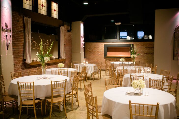 """The reception was decorated with white table linens and gold chiavari chairs. They used a mix of tall and short centerpieces to add some dimension to the room. """"The large venue was the perfect spot for us with the vintage old Hollywood style,"""" Shelby says. """"There was a huge dance floor as well as a bar that ran almost the entire length of the room. We knew this would be the perfect place for us to celebrate and party with our loved ones."""""""