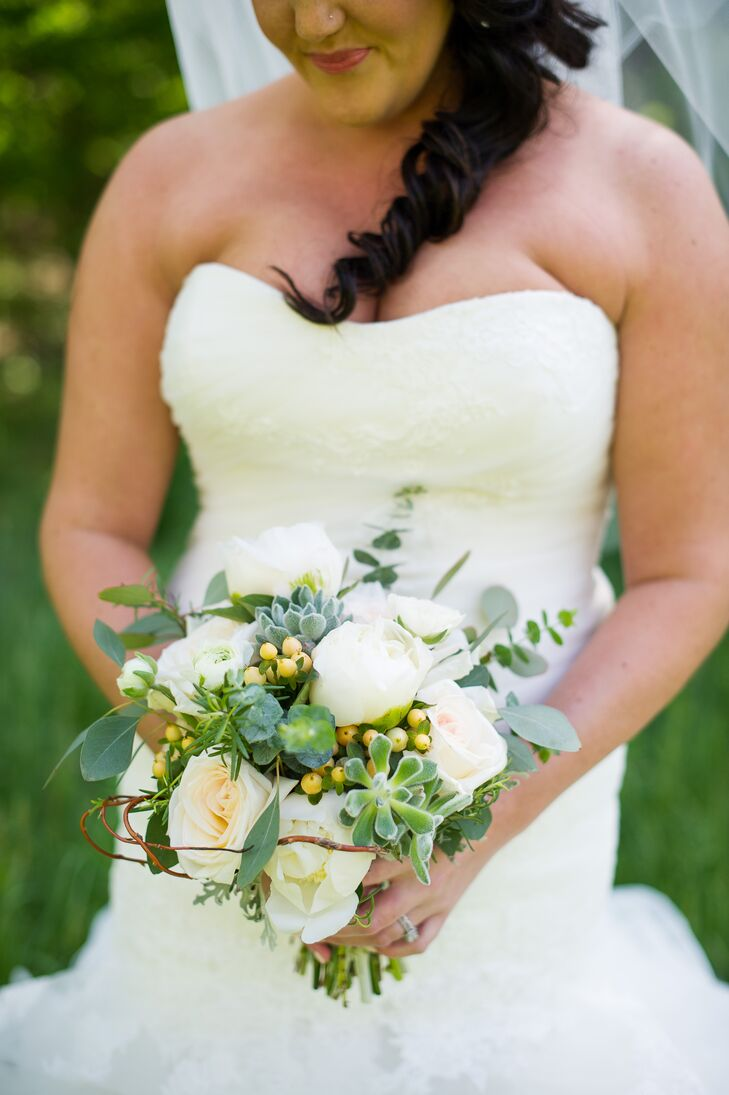 Wispy willow branches and sprigs of eucalyptus introduced a whimsical quality to Tori's romantic bridal bouquet. Succulents added an additional layer of texture and depth, while yellow hypericum berries and ivory roses, ranunculuses and peonies kept the bouquet feeling classic and elegant. To give the day a cohesive look, the same flowers were found in all of the centerpieces as well, with a few additional pops of color.