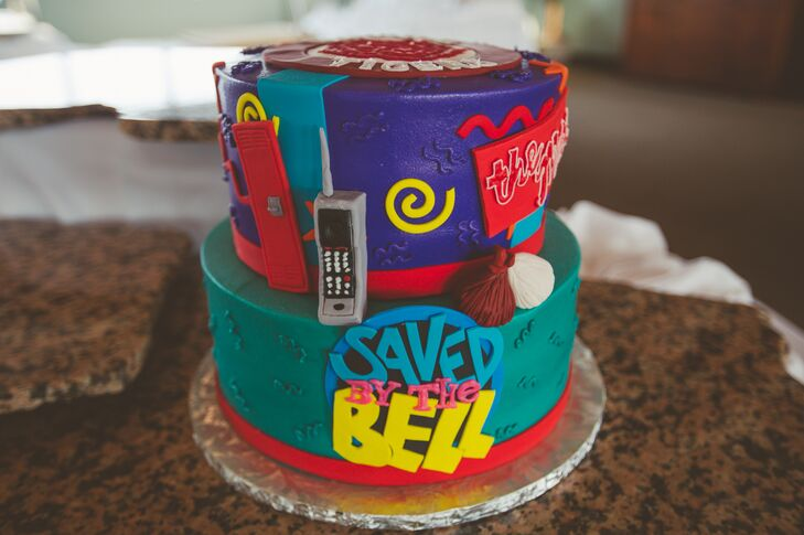 """The groom's cake was inspired by the 90s hit television show """"Saved by the Bell,"""" complete with Zack's infamous cell phone and a Bayside Tigers logo on top. The cake was chocolate with Butterfinger."""