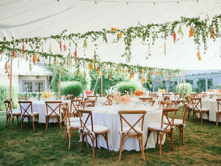 Flowers strung from ceiling of wedding reception tent
