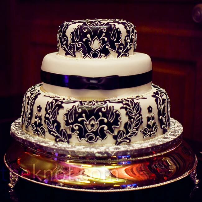 The three-tiered cake was covered in rolled chocolate and decorated with the couple's damask design.
