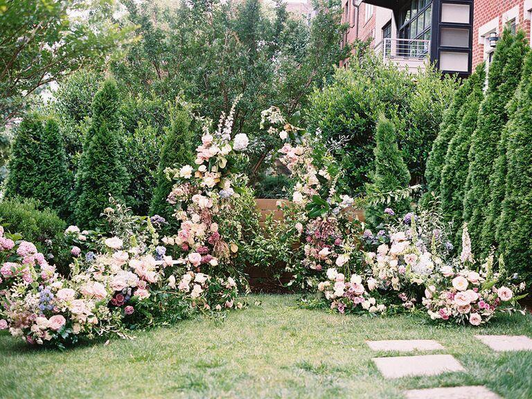 Whimsical pastel floral arrangement around oudoor wedding ceremony altar