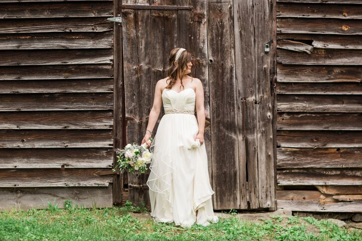 Emily wore a strapless ivory wedding dress with a romantic, flowy skirt. She styled her hair in a loose sideswept look with an ivory headband.