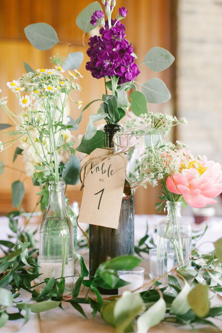 At the reception at Darby House in Galloway, Ohio, dining tables were marked with kraft paper tags that depicted numbers for guests to find their seats. The tables were decorated with stock and peony arrangements, mixed with Queen Anne's lace and other leafy greens. The flowers were arranged inside glass bottles, which were surrounded by more greenery.