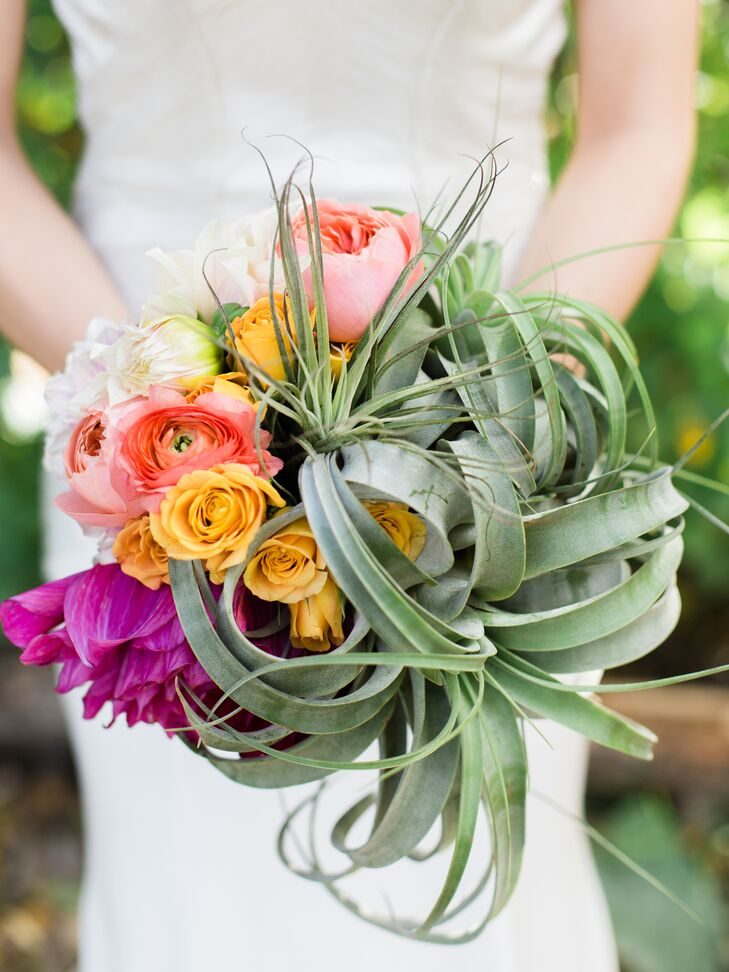Kelly held a bold, textural bouquet of king protea, air plants, roses and dahlias.