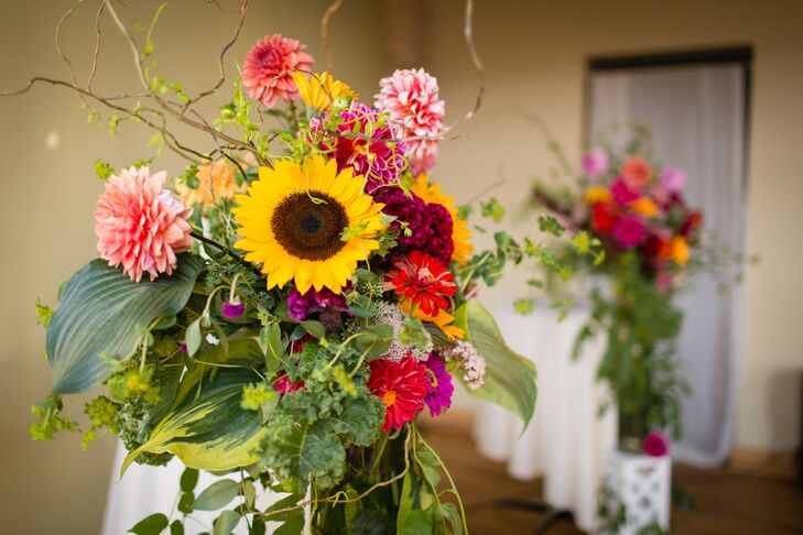 With the help of wedding planner Maddie Hughes from Ask for the Moon Events and florist Mickey O'Kane, Anna and Brandon exchanged vows between two lush, textured floral arrangements. We love the mix of yellow sunflowers with pink dahlias, red zinnias, burgundy coxcomb and plenty of textured greenery.