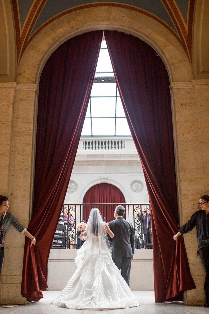 Elon entered the ceremony through deep red draped curtains on her father's arm, which took place inside the Columbus Museum of Art in Columbus, Ohio. Elon was walked down the aisle in her ivory strapless wedding dress designed by Hayley Paige, complemented by her traditional ivory tulle veil in her long hairstyle.