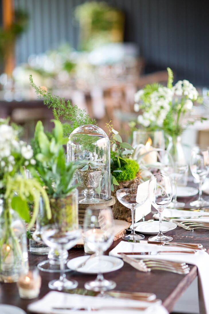 Each rustic wooden dining table had eclectic centerpieces of wild and potted greenery and wooden decor mixed with glassware and metallic accents.