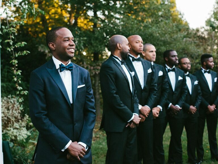 Groom smiling with groomsmen watching during wedding ceremony