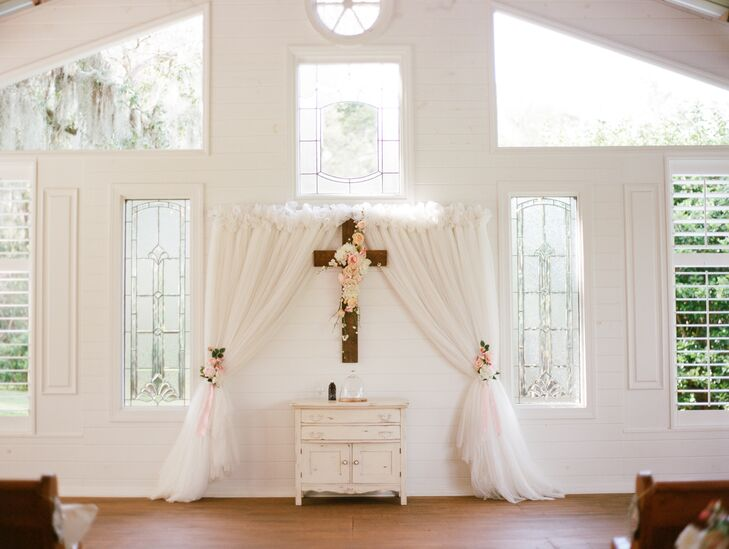 The ceremony altar was decorated with a chiffon curtain draped around the cross.