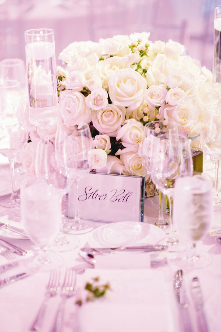 Lush white rose arrangements were placed on each table.