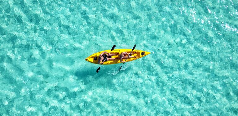 couple kayaking during their honeymoon during covid