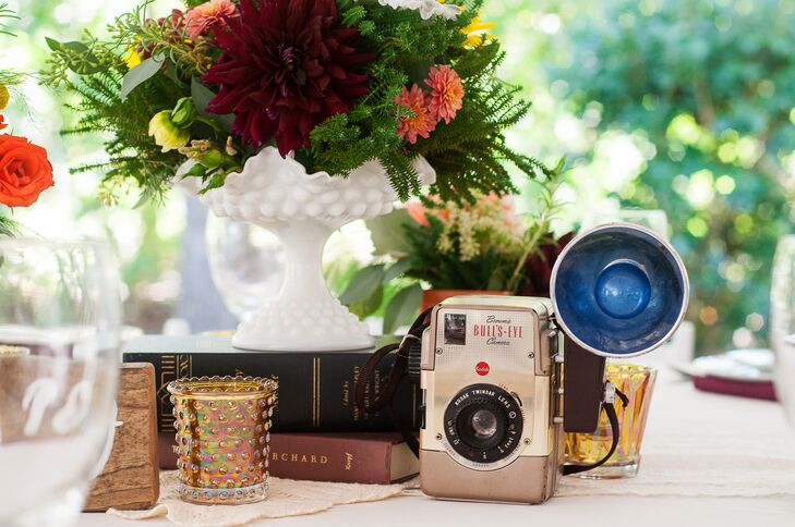 The bride collected vintage books, globes and cameras at flea markets and thrift shops to use as centerpiece vignettes.