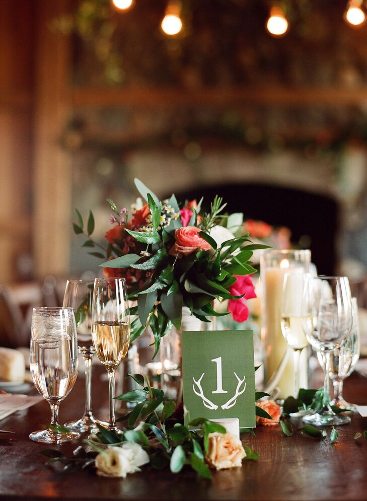 Mercury glass candleholders, glassware and vibrant wildflower arrangements created the reception tablescape.