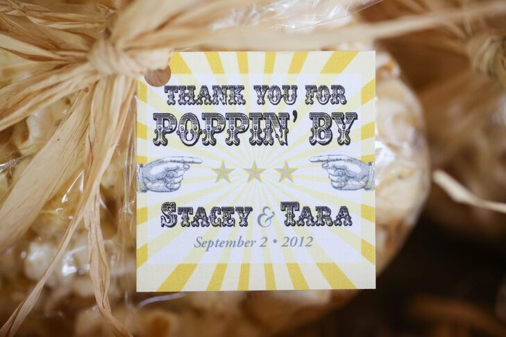 Adorable tags in the wedding colors were tied to the bags of popcorn on the favor table.