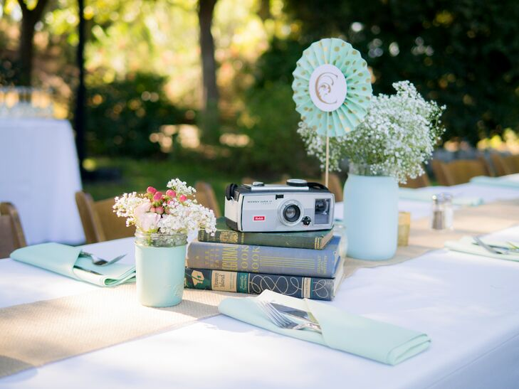 """Our centerpieces were antique books and cameras to represent our passions,"" says Angela. ""We are a husband and wife wedding photography team called ShootAnyAngle Wedding Photography, so we used some from our own collection and got more at flea markets and old book stores."