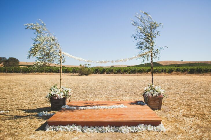 The ceremony took place at Lauren's family home, overlooking the rolling hills of Paso Robles. The ceremony altar was a simple wooden platform surrounded by white flower petals and two young trees with a string of white flowers between them serving as the backdrop.