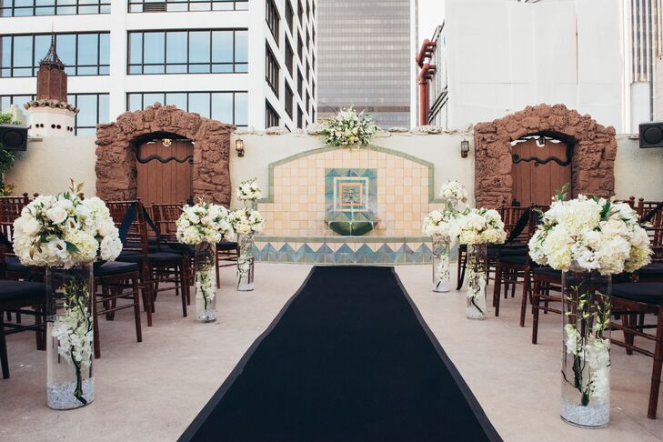 The ceremony took place in an Old Hollywood courtyard outdoors. The couple walked down the aisle on a dark aisle runner, lined by luxe over-size white bouquets of flowers.