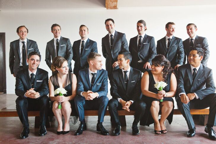 The couple glanced at each other as they posed with their wedding party, with the bridesmaids dressed in black short dresses and groomsmen in black tuxedos.