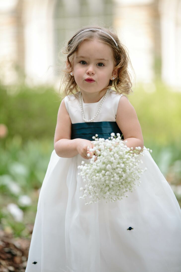 The adorable flower girls stole the show in silk taffeta dresses with navy rosebuds and carried small clusters of baby's breath.