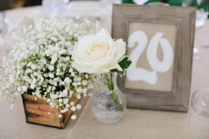 Hand-painted table numbers wooden flower crates filled with baby's breath lent a homey feel to the farm reception.