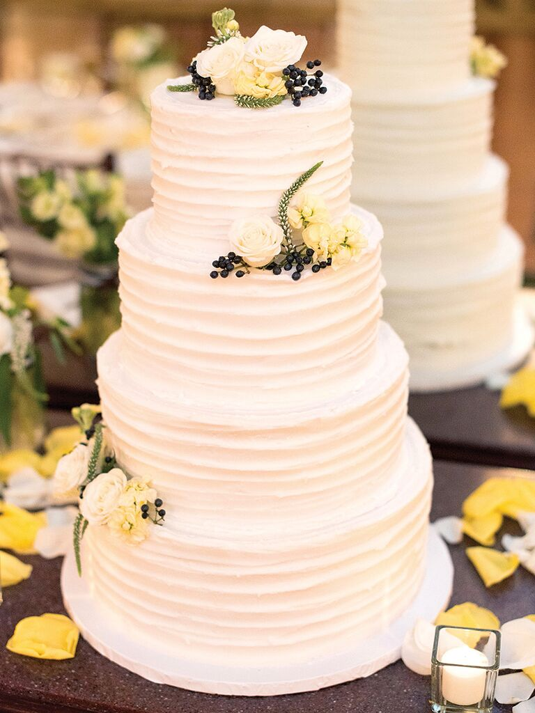Simple four-tier buttercream wedding cake with floral topper