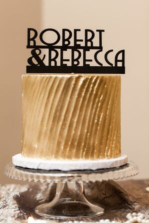 A Gold Art Deco Wedding Cake with a Personalized Cake Topper