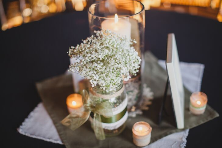 Mason jars were filled with baby's breath and displayed on the reception tables with pillar candles.