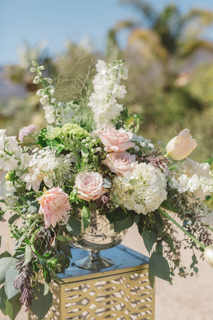 Blush pink garden roses, succulents, eucalyptus and ranunculus overflowed from small-stem glass-bowl vases, which sat on stands at the entrance of the aisle.