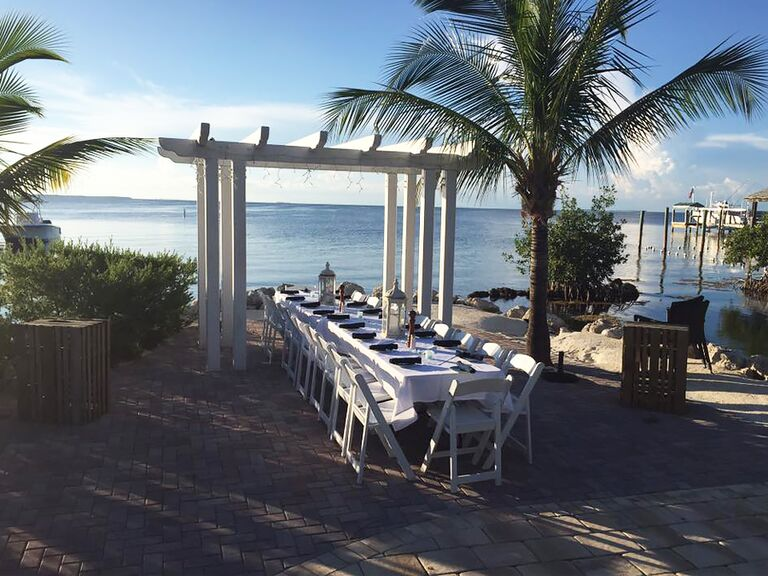 View of an outdoor table set for an event with a pergola and palm trees at Marker 88 in Islamorada Florida