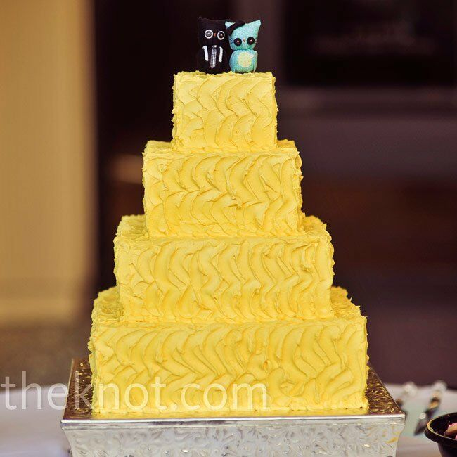 A simple, four-tiered yellow cake let the quirky owl cake topper shine.