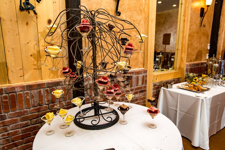 Kerry and Billy had a one-tier cake for the traditional cake cutting. Guests enjoyed their pieces of cake out of garnished martini glasses. Happy Cakes Bakeshop made three cake flavors, which were all displayed on a black wire tree. So modern!