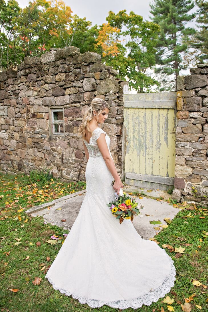 Courtney wore a lace wedding dress with cap sleeves, an illusion back and a long train. She wore her hair half up for the ceremony.