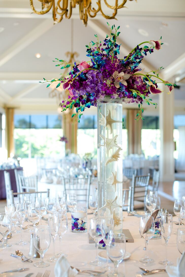 The couple decorated each table with a personalized photo table number and a colorful floral arrangement. Some included floating starfish and seashells inside a cylinder vase, topped with white orchids, pink roses, and purple and blue cymbidium orchids.