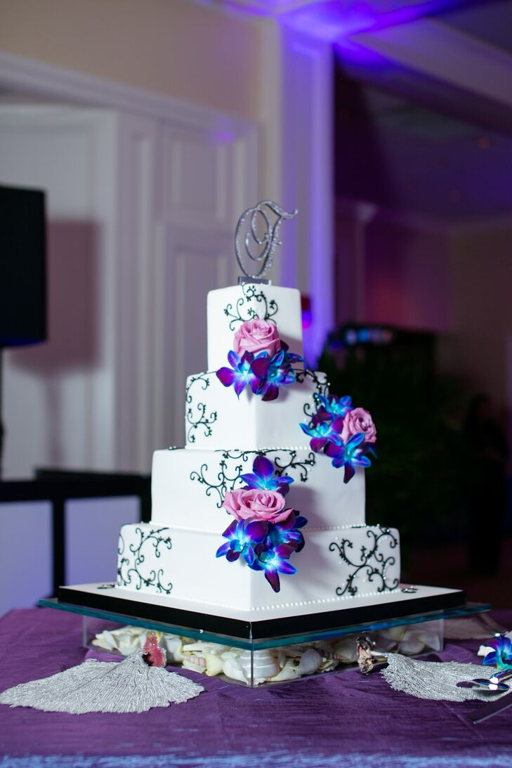 The couple had an elegant white four-tier wedding cake from Kakes by Karen with black piping, purple and blue orchids as well as pink roses made from icing on each tier. The clear base of the cake was filled with seashells.