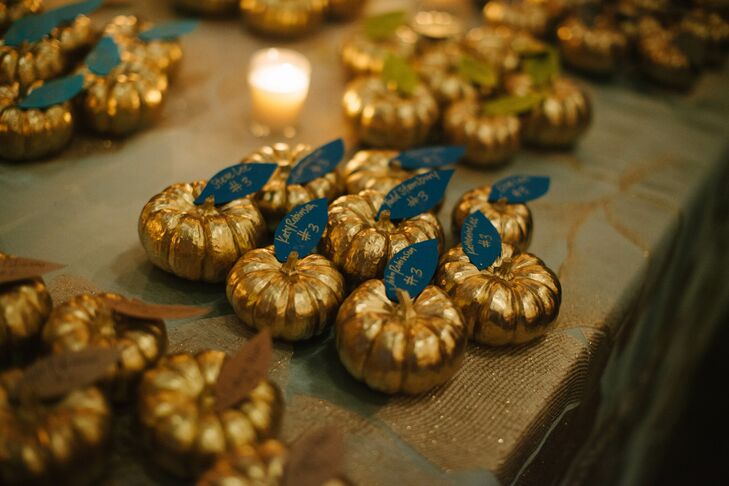 As a nod to the season, metallic painted mini pumpkins served as escort cards with table assignments written on paper leaves.