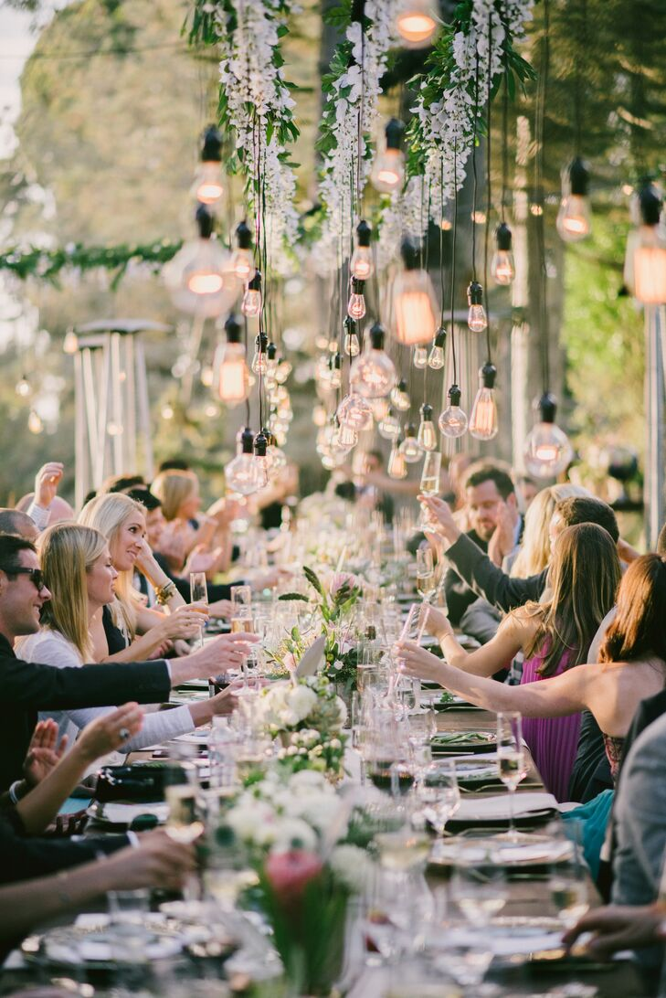 "The U-shaped seating arrangement sat under a wooden frame from which a garland, white flowers and Edison lightbulbs hung. ""The lights provided a beautiful visual, which evolved as we lost daylight,"" Rory says."