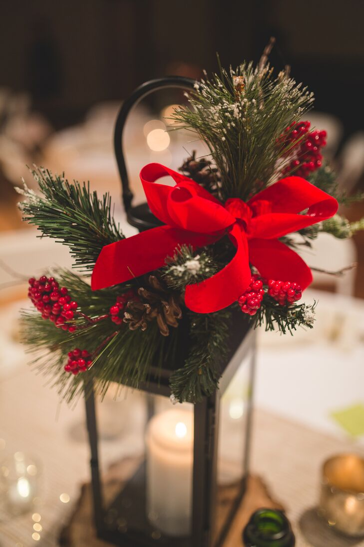 Elizabeth and Mason's lantern centerpieces were adorned with pine, red berries and red ribbons following the Christmas-themed wedding day.