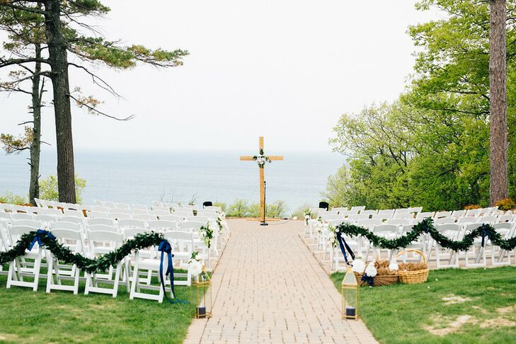 Other than a large handmade cross, a navy ribbon, garlands of ruscus and simple floral arrangements on aisle seats, the ceremony decor was kept simple so as not to take away from the natural beauty of Lake Michigan.