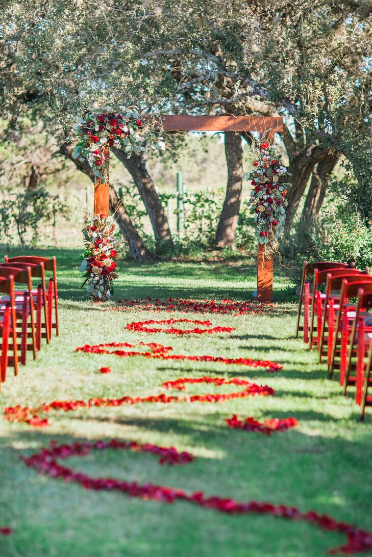 A pattern of red rose petals decorated the ceremony aisle, leading to the wooden ceremony arch nestled under a cluster of oak trees.