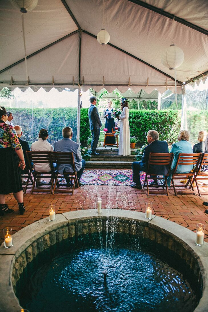 "The ceremony took place in Michael's parents' backyard, complete with a brick courtyard, a water fountain and white Chinese lanterns hanging from the tent's ceiling. A colorful Boucherouite rug separated the 57 guests from the couple. Originally, half of the wedding and part of the reception were going to be outdoors, but a week before the celebration, with rain in the forecast, the couple rented tents. That turned out to be a good move, because it rained (and rained and rained). Tonya jokes that if rain is good luck on your wedding day, ""our cup runneth over."""