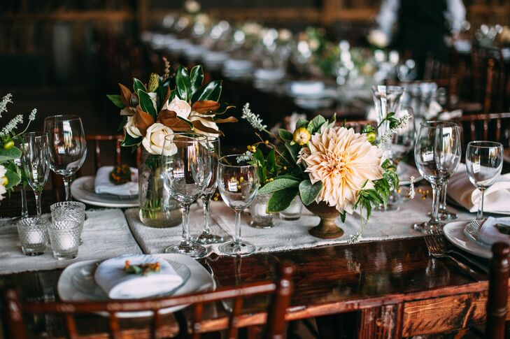 The farmhouse dining tables were adorned with arrangements of magnolia leaves, ivory roses and stunning dinner plate dahlias.