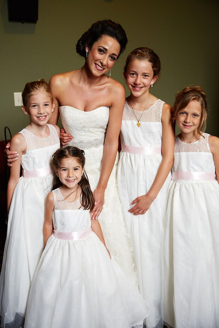 Maria had four flower girls for her traditional Greek Orthodox wedding. They wore white tulle-and-lace dresses to match Maria's wedding dress. A soft satin blush belt completed their look with a subtle pop of color.
