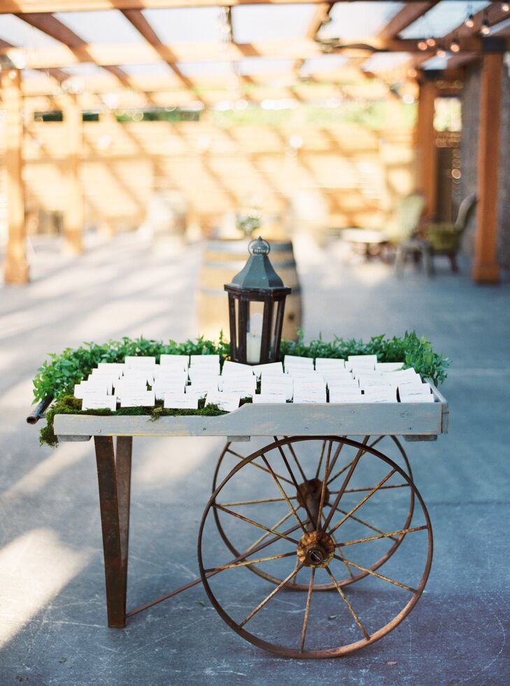 A rustic wooden table with wheels at the bottom held up the display of white escort cards, arranged on a grassy surface with a lantern on top.