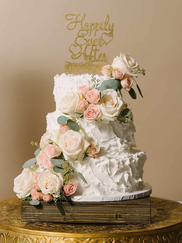 Romantic textured buttercream wedding cake with roses and seeded eucalyptus