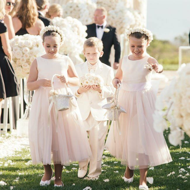 The flower girls wore blush mid-length dresses with tulle skirts and ivory rose flower crowns.