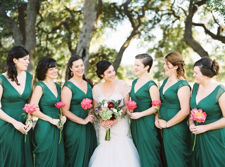 """The bridesmaids wore deep green V-neck dresses, holding a single pink peony for a pop of color. """"To capture the deep green of live oaks in the Texas Hill Country, the girls wore the same flowing dark green chiffon gowns we purchased from my hometown's Bella Bridesmaid shop,"""" Ann says. """"The dresses went well with everyone's skin tones and body types."""""""