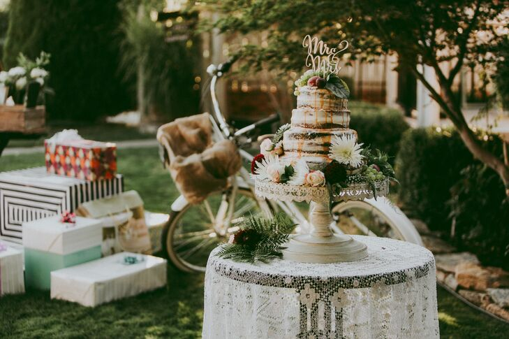 """At the reception, a gift table and a homemade wedding cake served as focal points. """"The cake was a loving masterpiece of banana chocolate chip, vanilla icing and drizzled salted caramel sauce, and it was topped with flowers and various fruits and berries. It upstaged everything."""""""