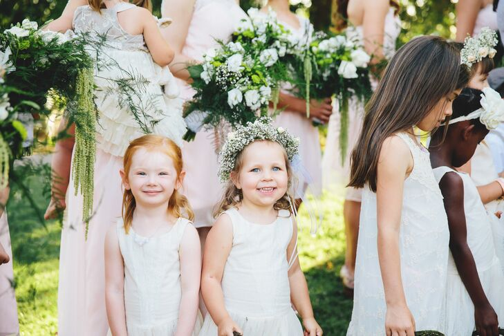 "Two flower girls smiled at the camera, who wore ivory dresses and flower crowns. ""We had 23 barefoot children walk down the aisle, all of who were either nephews, nieces or very close family friends,"" says Anna. ""Those too young to walk on their own were carried by their fathers."""