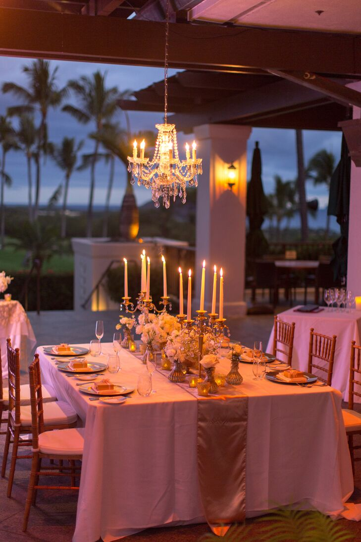 The reception took place on the patio of Kukahiko Estate, where an elegant chandelier hovered over the reception dining table. Candelabras holding up long white candlesticks created a romantic display for Steph, Nick and their guest list of four.